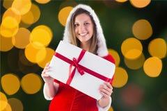 Mujer hermosa en el traje de santa que sostiene un regalo Fotografía de archivo libre de regalías