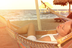 Mujer hermosa en el vestido blanco en hamaca en la playa soleada Fotos de archivo
