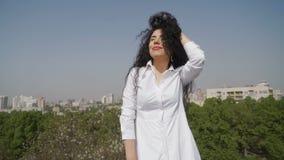 Mujer hermosa en el vestido blanco que presenta para la cámara en el fondo verde de la ciudad almacen de metraje de vídeo