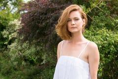 Mujer hermosa en el vestido blanco que se relaja en el parque imágenes de archivo libres de regalías