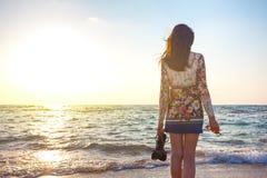 Mujer hermosa en el vestido colorido que se coloca en la playa cerca del océano y que considera lejos la puesta del sol imagenes de archivo