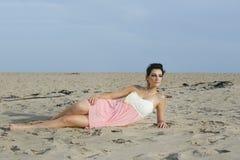 Mujer hermosa en el vestido femenino que miente en la arena del desierto Fotos de archivo