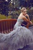 Mujer hermosa en el vestido lujoso que se sienta en banco en parque imagenes de archivo