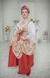 Mujer hermosa en el vestido medieval que sostiene la rosa del rosa imagen de archivo