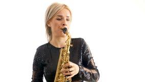Mujer hermosa en el vestido negro del concierto que juega una melodía en melodía del saxofón aislada sobre el fondo blanco almacen de video