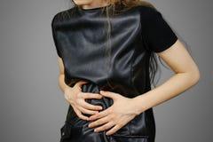 Mujer hermosa en el vestido negro que tiene su período Muchacha triguena en la chaqueta de cuero Imagen de archivo libre de regalías