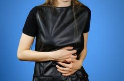 Mujer hermosa en el vestido negro que tiene su período Muchacha triguena en la chaqueta de cuero Foto de archivo libre de regalías