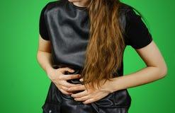 Mujer hermosa en el vestido negro que tiene su período Muchacha triguena en la chaqueta de cuero Imagenes de archivo