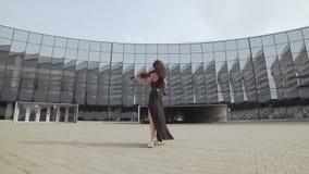 Mujer hermosa en el vestido negro que toca el violín cerca del edificio de cristal Concepto del arte metrajes