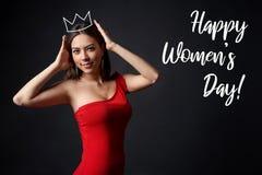 Mujer hermosa en el vestido rojo que apoya su corona fotografía de archivo