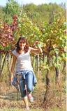 Mujer hermosa en el viñedo en otoño con las uvas Imágenes de archivo libres de regalías