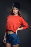 Mujer hermosa en estilo del hip-hop con el sombrero en la cabeza contra la pared negra Fotos de archivo