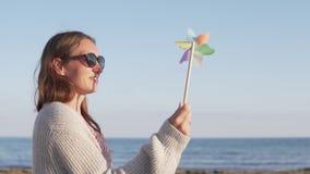 Mujer hermosa en gafas de sol el las vacaciones de verano que juegan con el molino de viento del juguete almacen de metraje de vídeo