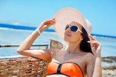 Mujer hermosa en gafas de sol y el sombrero blanco que toma el sol en la playa Foto de archivo libre de regalías
