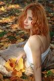 Mujer hermosa en hojas amarillas Fotos de archivo libres de regalías