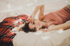 Mujer hermosa en la cama, interior de la Navidad, disfrute Fotografía de archivo