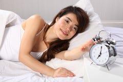 Mujer hermosa en la cama que alcanza para el reloj de alarma foto de archivo