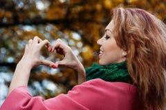 Mujer hermosa en la capa rosada que muestra el corazón en el parque Imágenes de archivo libres de regalías