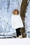 Mujer hermosa en la chaqueta blanca en un parque nevoso imagen de archivo libre de regalías