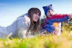 Mujer hermosa en la hierba con su hijo Foto de archivo libre de regalías