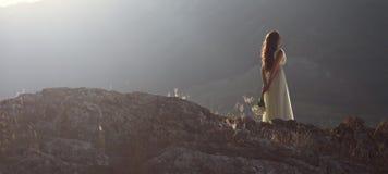 Mujer hermosa en la montaña en la puesta del sol Fotos de archivo