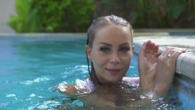 Mujer hermosa en la piscina que mira a la c?mara y a la c?mara delantera sonriente Mujer atractiva que presenta en agua azul almacen de metraje de vídeo