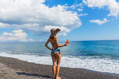 Mujer hermosa en la playa con un cóctel Imágenes de archivo libres de regalías