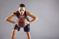 Mujer hermosa en la ropa de deportes que juega a baloncesto fotos de archivo