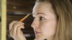 Mujer hermosa en la toalla, pinturas sus cejas delante del espejo almacen de metraje de vídeo