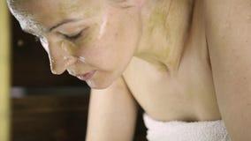 Mujer hermosa en la toalla que salpica su cara la muchacha lava apagado la máscara de la cara Cuidado de piel y balneario casero almacen de video
