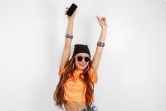 Mujer hermosa en las gafas de sol que llevan en sombrero negro y música que escucha de la camiseta anaranjada y que bailan cerca  Fotos de archivo libres de regalías