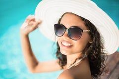 Mujer hermosa en las gafas de sol que se sientan por la piscina Imagen de archivo libre de regalías