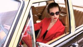 Mujer hermosa en las lentes de sol negros que se sientan en el coche retro y que miran a la izquierda metrajes