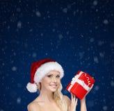 Mujer hermosa en las manos del casquillo de la Navidad presentes Imagen de archivo libre de regalías