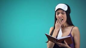 Mujer hermosa en libro de lectura de los pijamas en la cama, el caer dormido después de día cansado almacen de metraje de vídeo