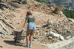 Mujer hermosa en los pantalones cortos y en el casquillo enarbolado rojo con una carretilla para el cemento
