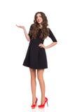 Mujer hermosa en Mini Dress Presenting Product negro Fotografía de archivo libre de regalías