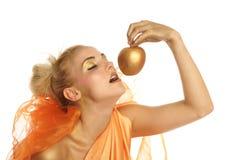 Mujer hermosa en oro con la manzana del oro Fotografía de archivo libre de regalías