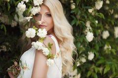 Mujer hermosa en parque cerca de las rosas florecientes de Bush Imagenes de archivo