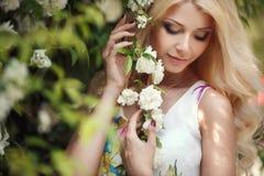 Mujer hermosa en parque cerca de las rosas florecientes de Bush imágenes de archivo libres de regalías