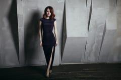 Mujer hermosa en retrato gris de la moda del fondo del vestido oscuro largo imagenes de archivo