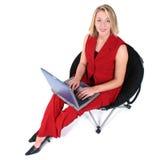 Mujer hermosa en rojo con la computadora portátil en silla negra fotografía de archivo