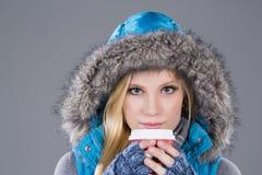 Mujer hermosa en ropa del invierno que bebe el café Imágenes de archivo libres de regalías
