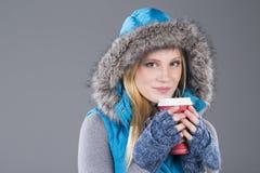 Mujer hermosa en ropa del invierno que bebe el café Foto de archivo libre de regalías