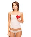 Mujer hermosa en ropa interior del algodón y corazón rojo Imagenes de archivo