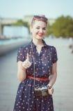 Mujer hermosa en ropa vintage con la cámara retra que muestra el th Imagen de archivo
