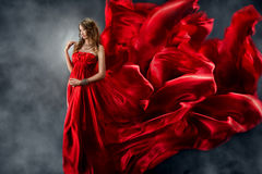 Mujer hermosa en seda que agita roja como llama fotos de archivo