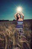 Mujer hermosa en sol de la explotación agrícola del campo de trigo Imagenes de archivo