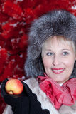 Mujer hermosa en sombrero de piel del invierno en el árbol de navidad rojo del fondo Imágenes de archivo libres de regalías