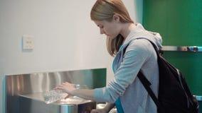 Mujer hermosa en terminal de aeropuerto Agua cercana derecha del dibujo de la fuente de consumición en botella plástica almacen de metraje de vídeo